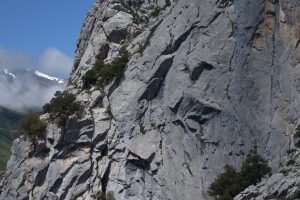A climber dwarf by the size of the wall, the orange dot on the bottom right. Near Agero in picos De Europa.