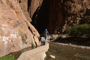 Balancing along the irrigation canal to reach a climbing area in Todra Gorge