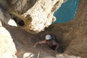 Tash toping out through the hole in the pirates cave on Parle, 6a, Toix.